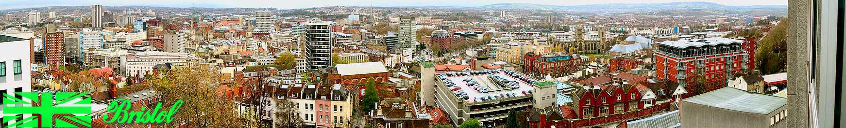 A panoramic view looking over a                                 cityscape of office blocks, old                                 buildings, church spires and a                                 multi-story car park. In the distance                                 hills.
